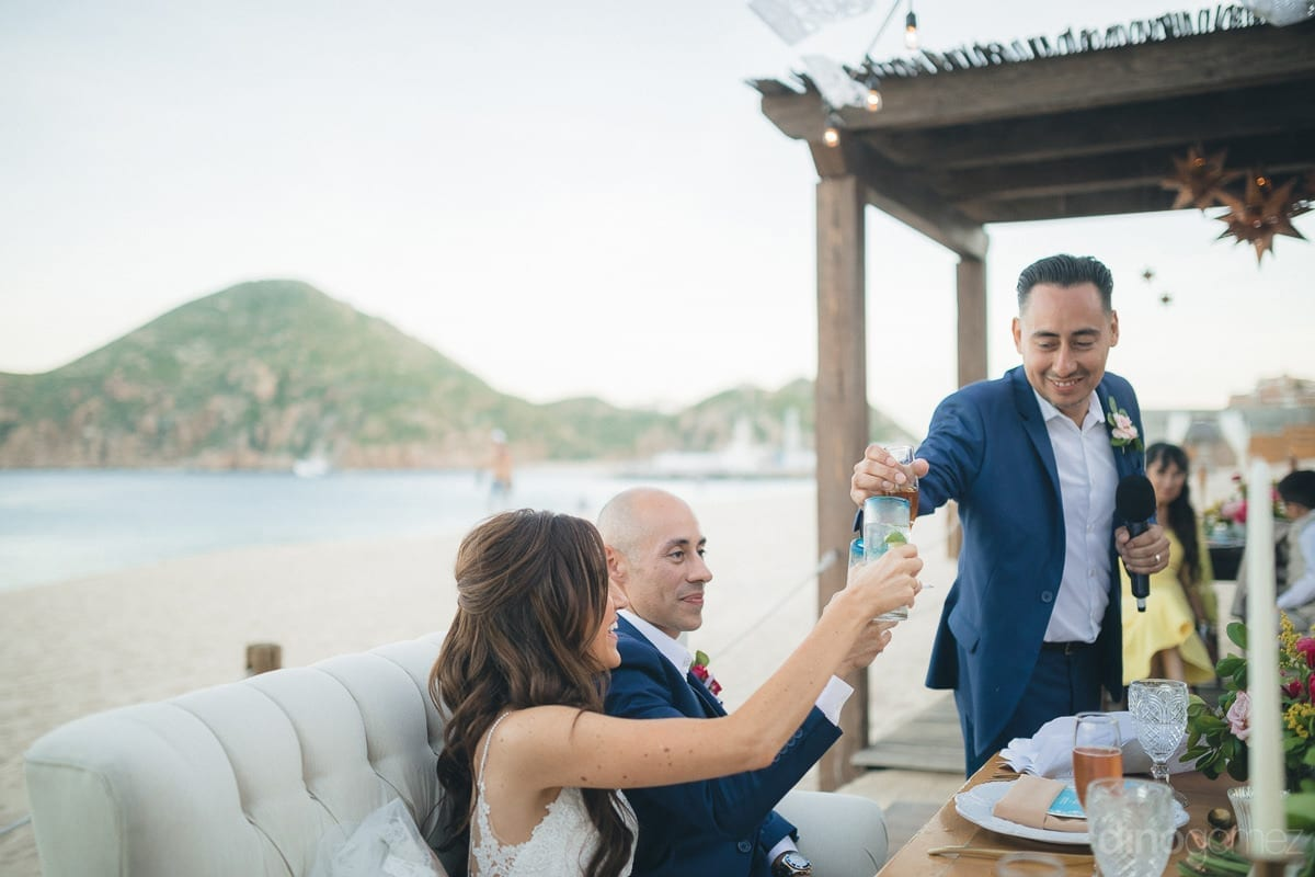 A gentleman holding mike in one hand is raising a toast to the newly married couple sitting at the beachside- Nikki and David