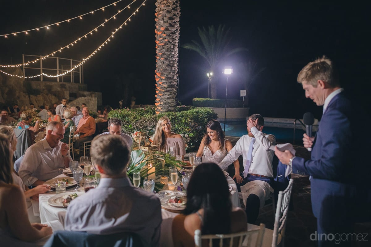 The Wedding Guests Can Be Seen Sitting Aroung Circular Tables And Listening To The Speech Of A Gentleman At The Reception Party- Kathleen & Kevin