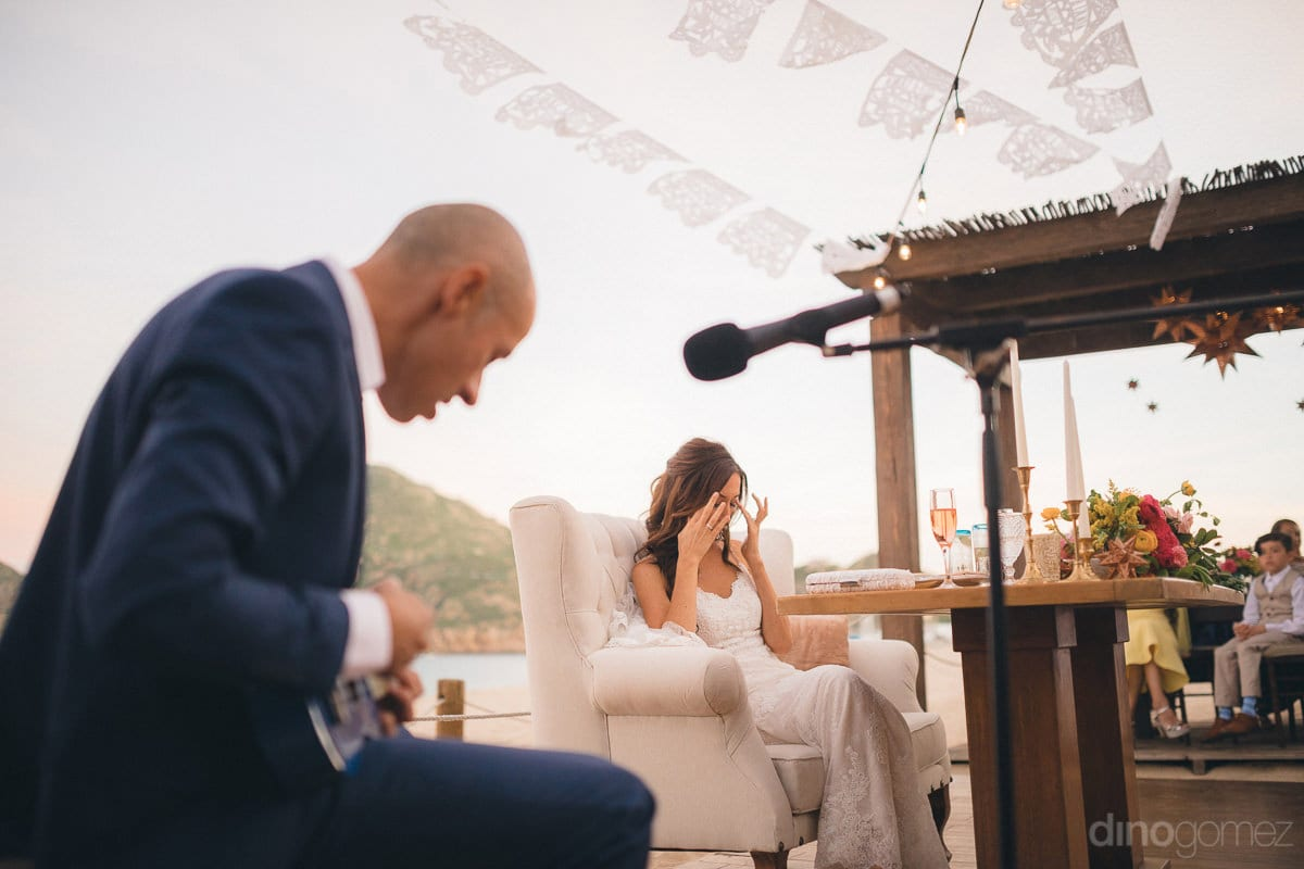 A lovely sideview capturing a gentleman singing in the mike and pretty bride wipping off her eyes is captured- Nikki and David