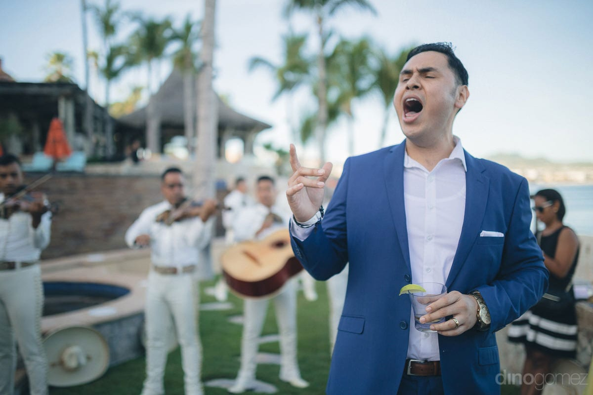 A handsome man dressed in blue suit and holding a glass of drink is singing along with the musicians at the evening party of the couple- Nikki and David