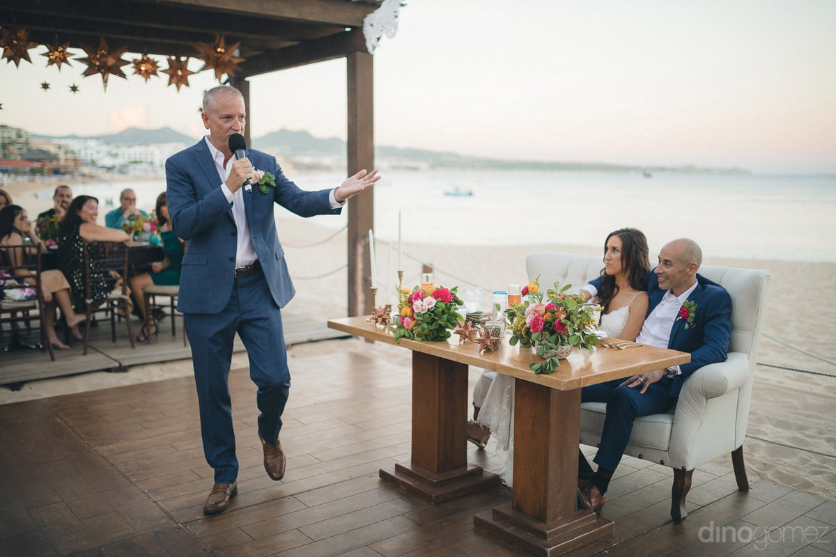 A gentleman holding a mike is saying a few words for the newly married couple standing at the wooden floor during the reception party- Nikki and David
