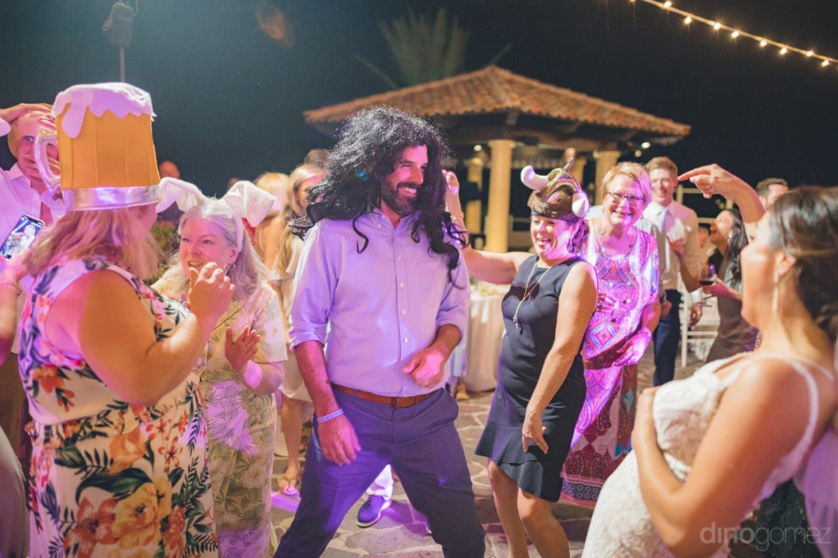 Wedding guests can be seen wearing head masks and enjoying the dance at the reception party- Kathleen & Kevin