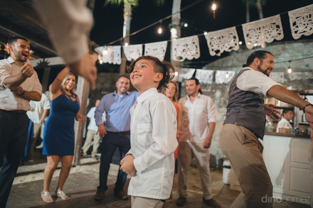 A cute young boy is all excited to dance with the wedding guests at the reception party- Nikki and David