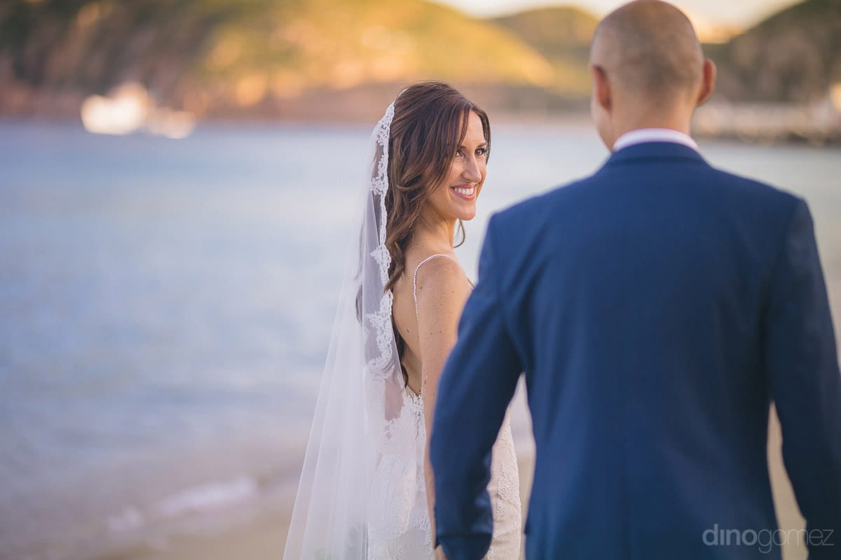 The pretty bride and handsome groom is walking along the beachside wearing broad smile and holding each other hands- Nikki and David