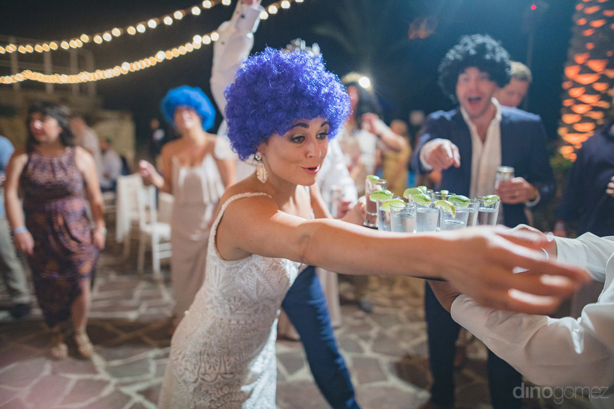 Gorgeous young bride wearing blue hair wig can be seen picking glasses of shots at the reception party- Kathleen & Kevin