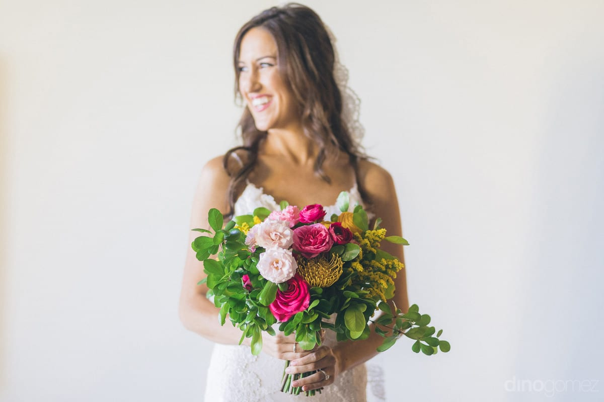 A beautiful picture of the bride dressed in amazing white wedding gown and holding a colorful bouquet of roses is taken- Nikki and David