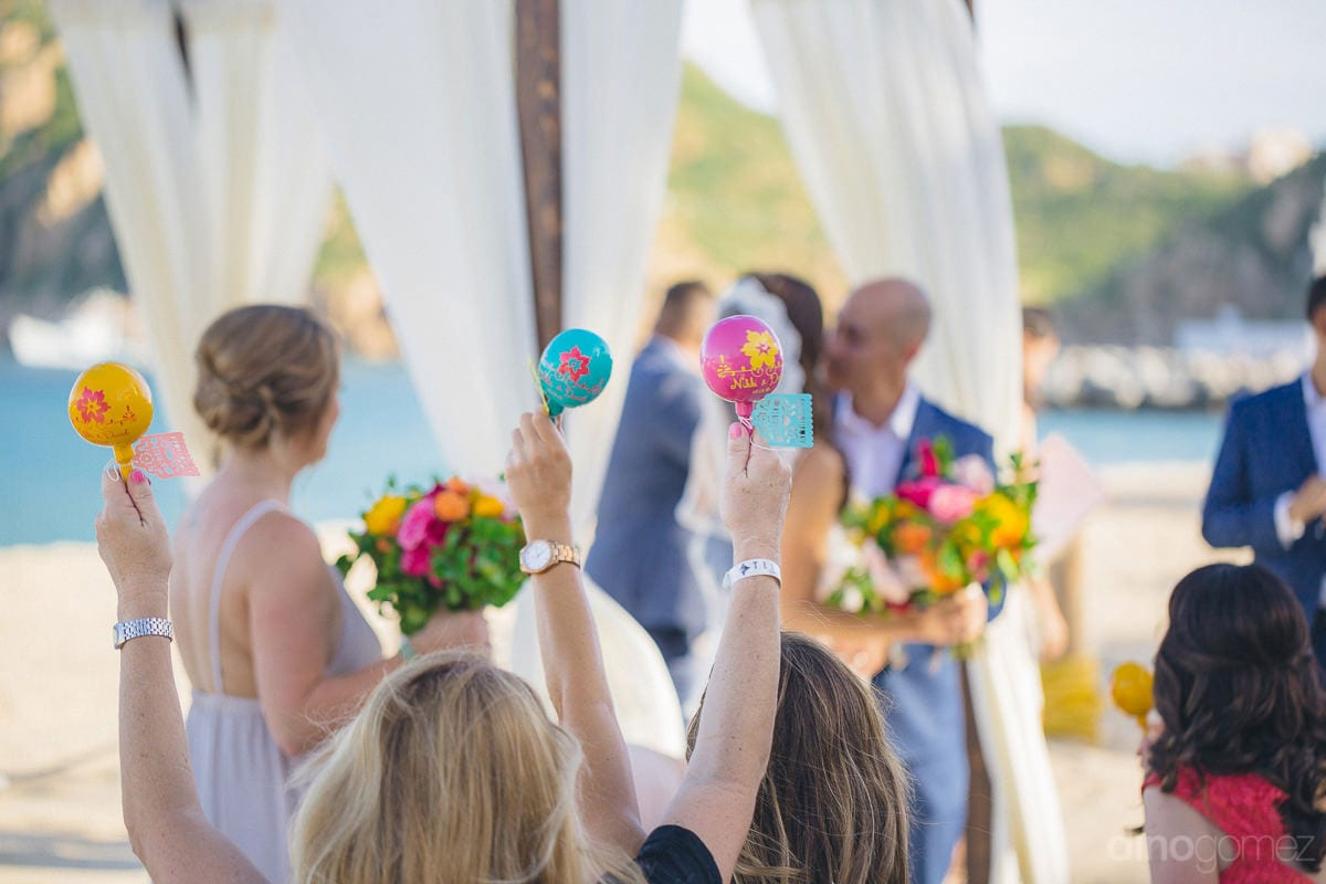 The Headline! The picture captures the wedding guests holding props up in the air to make noise during the wedding ceremony of the couple- Nikki and DavidUSE KEYWORDS