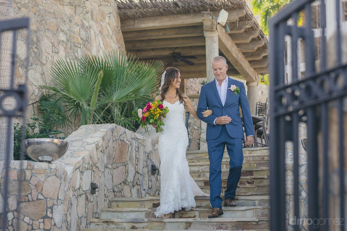 Gorgeous bride dressed in white gown is walking down the stairs with broad smile on her face to reach the wedding stage- Nikki and David