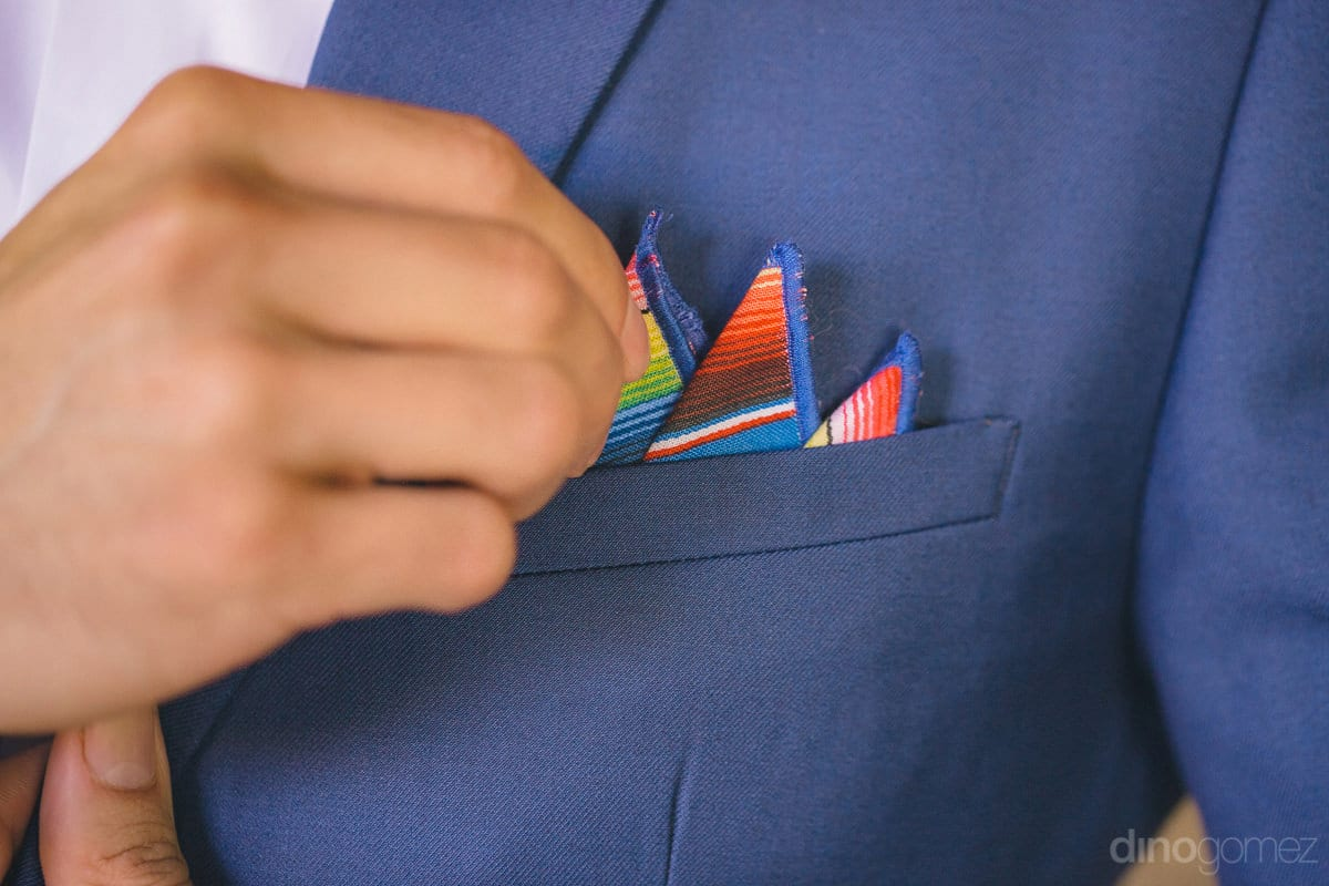 A closeup of a gentleman setting his blue coats pocket sqaure is taken- Nikki and David