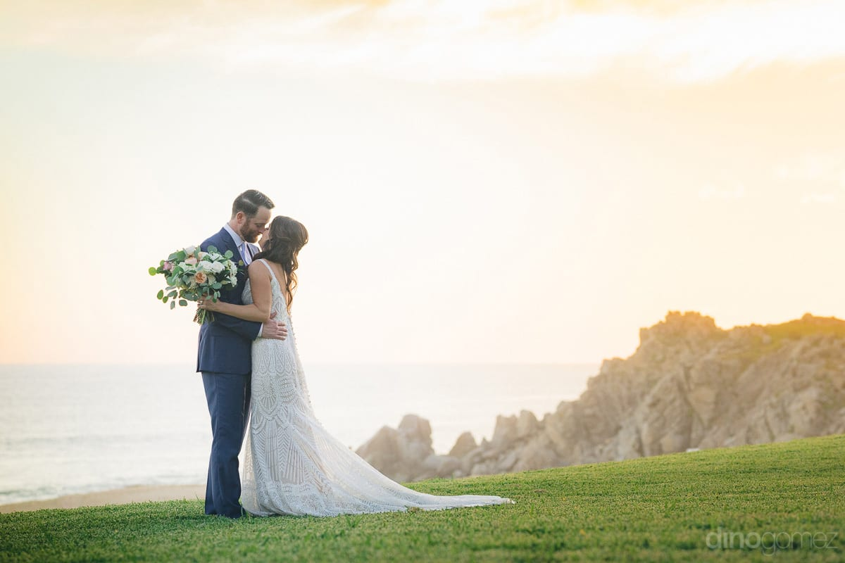 The Newly Married Couple Is Hugging Each Other While Standing On The Lush Green Grass Alongside The Ocean- Kathleen & Kevin