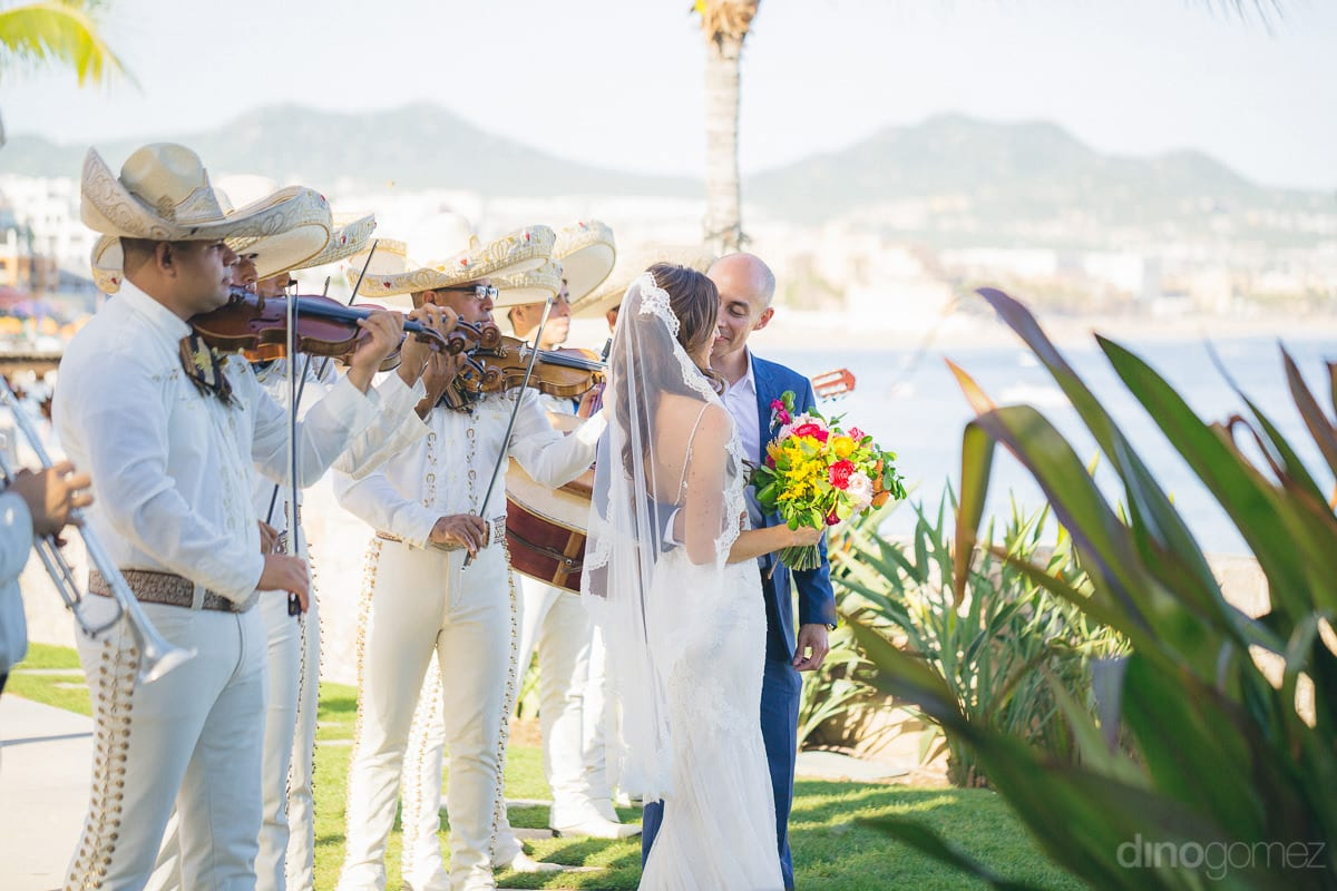 A beautiful picture of the couple standing at the lush green grass of the beachside lawn along with the musicians is taken- Nikki and David