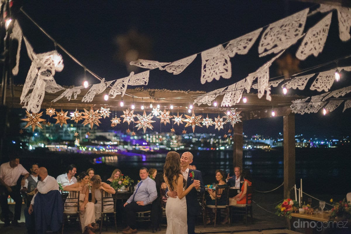 A lovely view of the evening reception party of the couple along the beachside while couple dancing together is captured in the picture- Nikki and David
