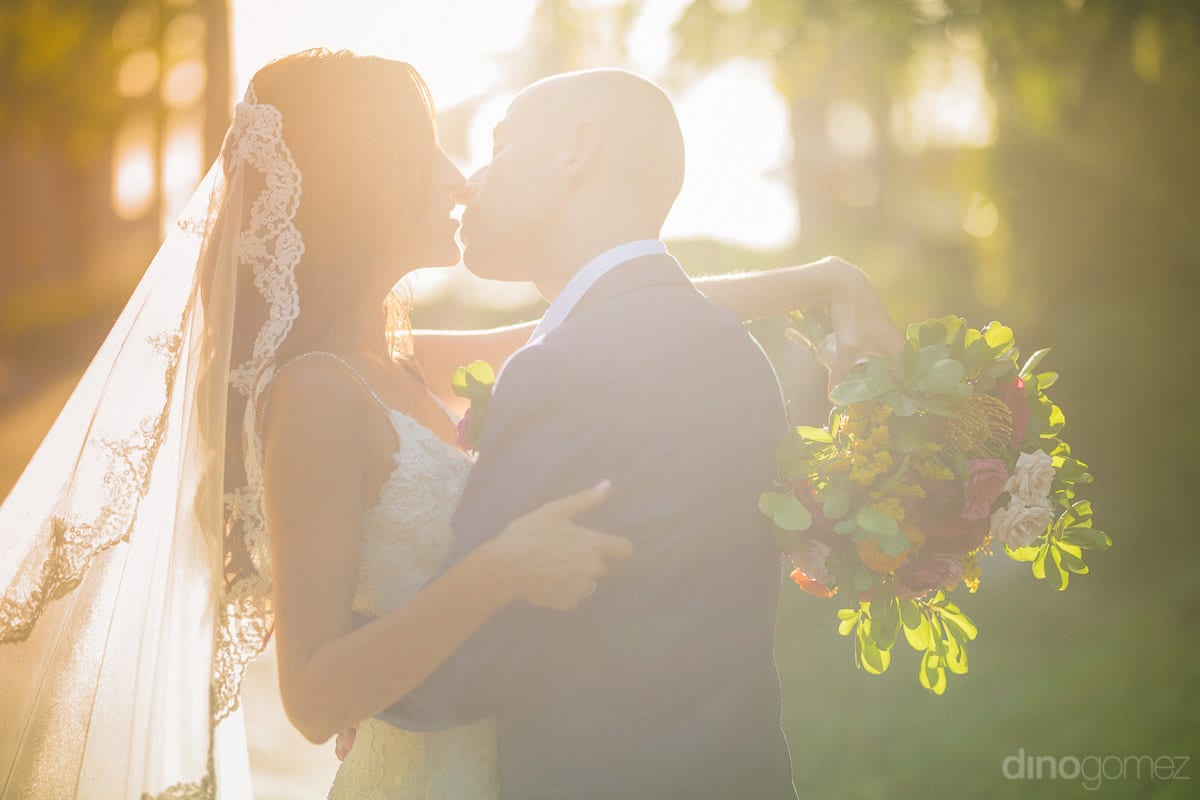 The lovely bride and groom are about to kiss each other at the sunset among lovely green plants- Nikki and David
