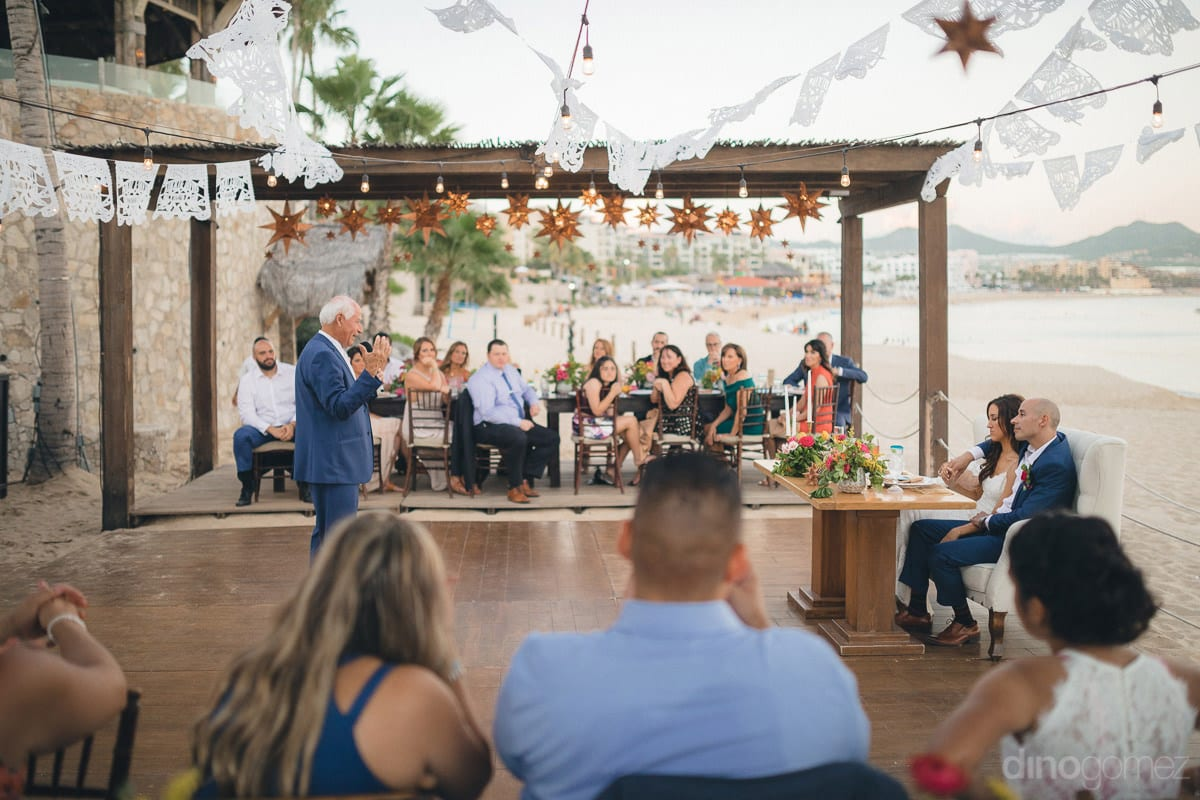 A gentleman is speaking a few words for the lovely newly married couple in the presence of all the wedding guests at the beachside- Nikki and David