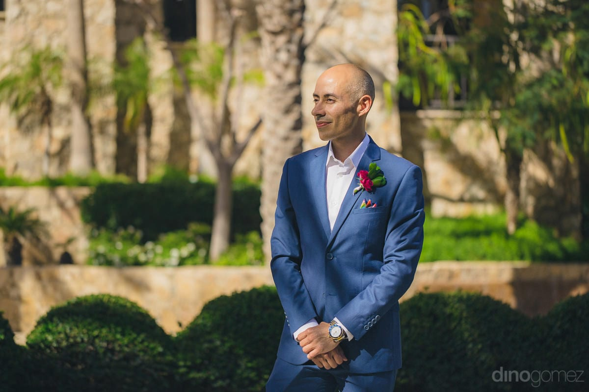Handsome groom is standing in the lush green garden wearing a blue suit and posing amazingly for the camera- Nikki and David
