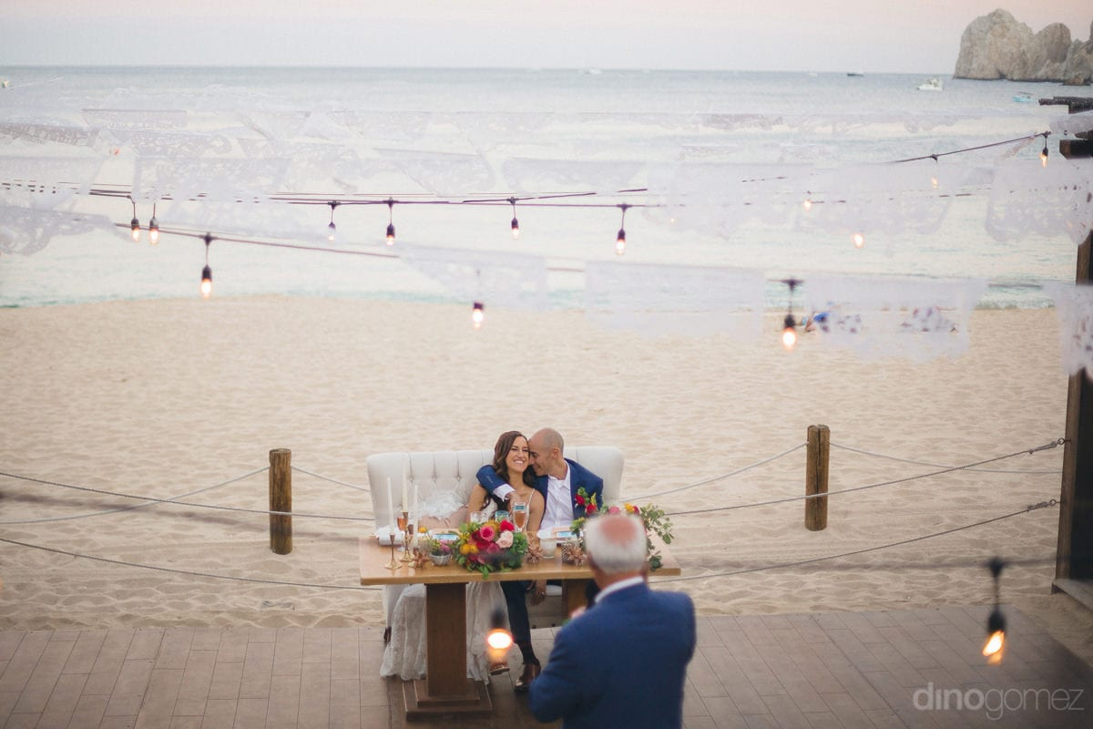 A beautiful shot of the lovely couple sitting on a couch on the beach sand under lovely lights is captured in the picture- Nikki and David