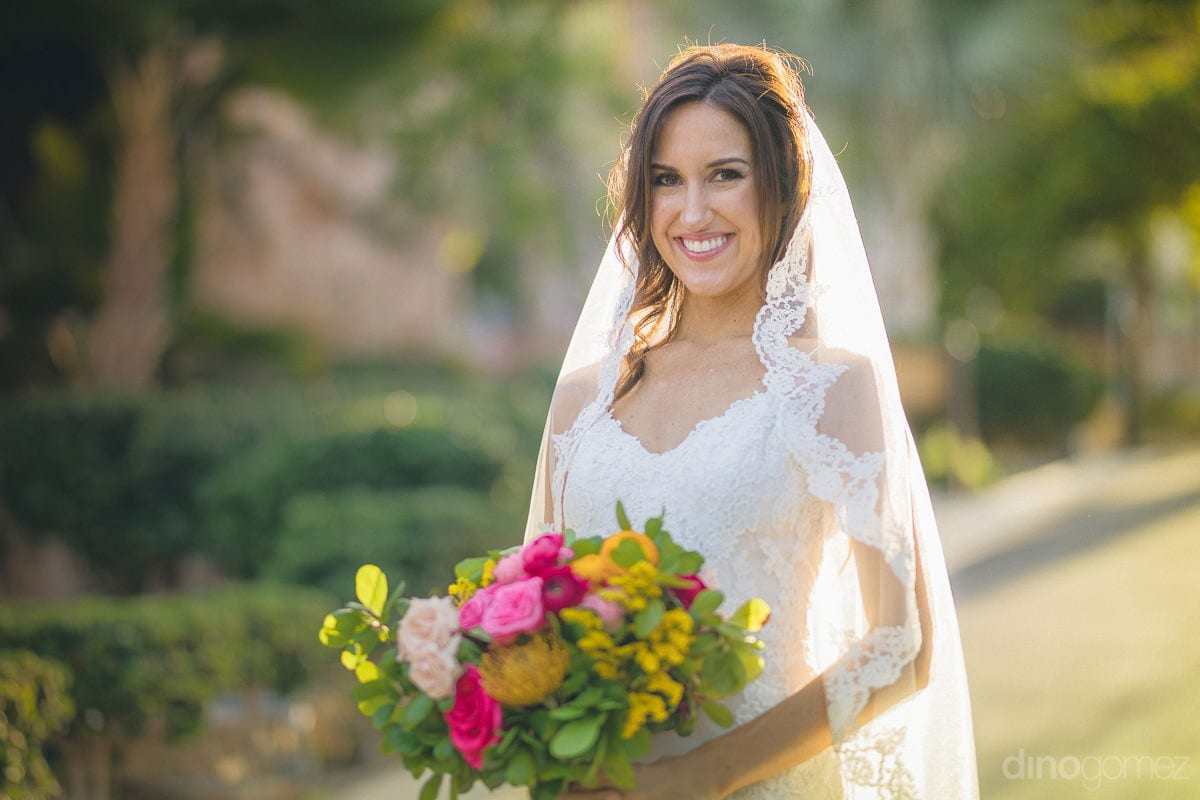 The bride is looking angelic in her beautiful white wedding gown holding her colorful bouquet- Nikki and David	The bride is dressed in her white wedding gown and is looking just perfect holding her colorful bouquet of roses. She is standing in a lawn full