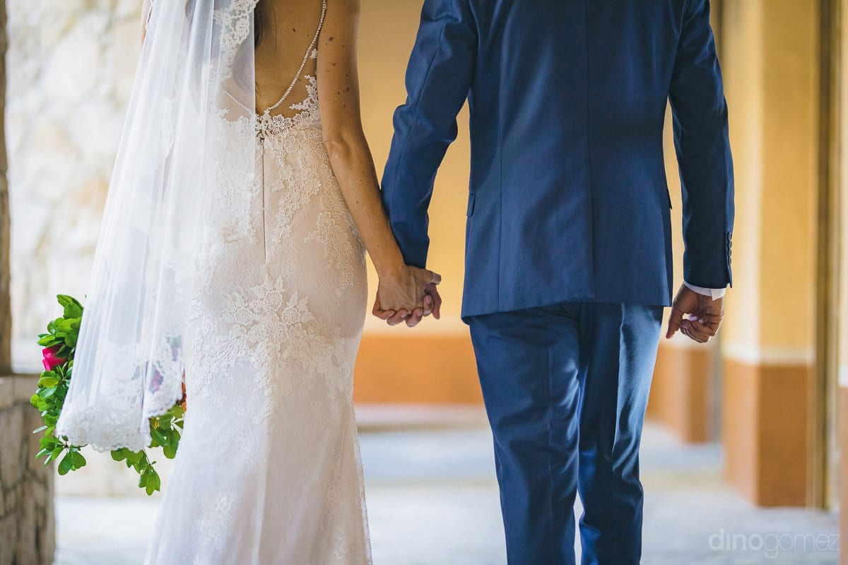 The picture shows the back side view of the lovely couple walking in a corridor holding each others hands- Nikki and David