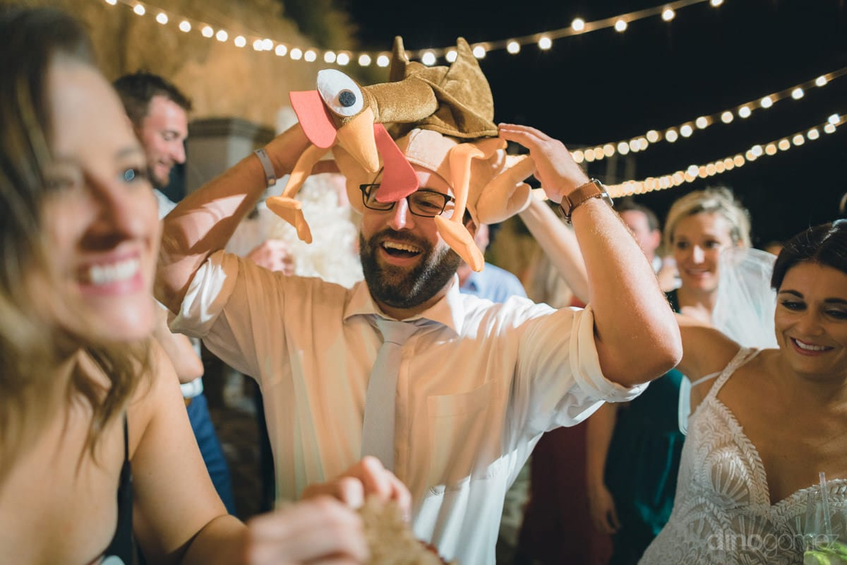 A Young Man Can Be Seen Putting On A Funny Animal Face Mask And Having Fun With His Friendsat The Reception Party- Kathleen & Kevin
