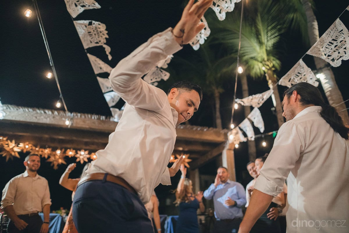 A young man is dancing with full energy at the evening reception party of the couple- Nikki and David