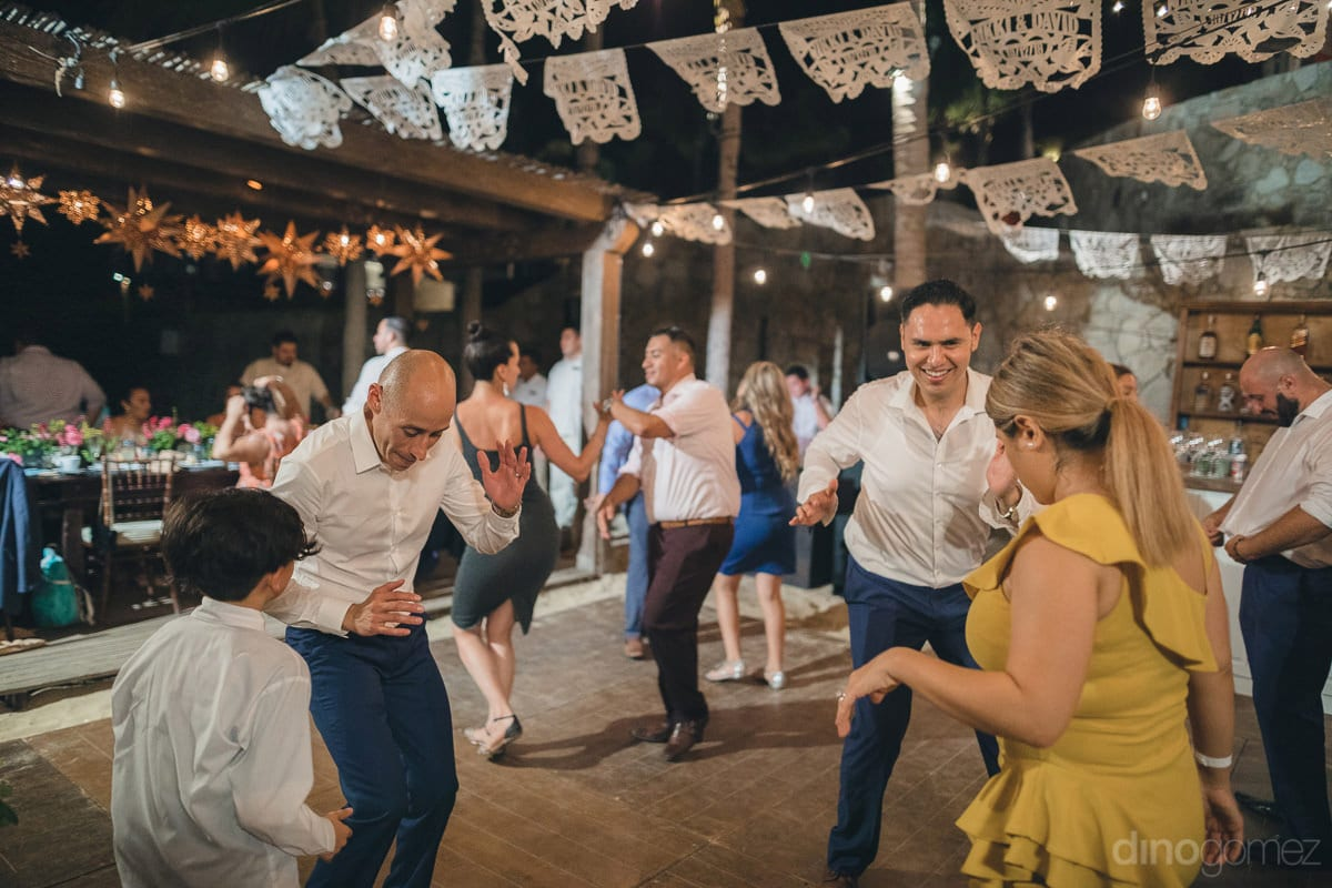Handsome groom is dancing with the wedding guests at the evening reception party- Nikki and David