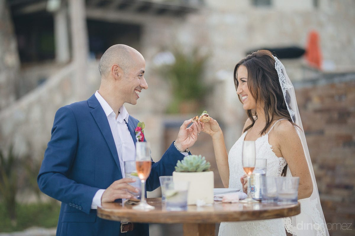 Newly married couple is standing around a circular table and sharing a pice of sweetdish with each other- Nikki and David