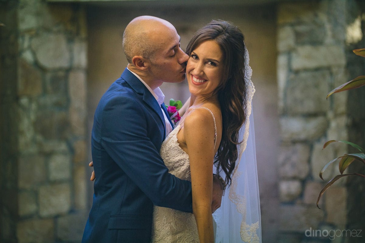 The handsome groom is kissing the bride on her cheeks while standing at a secluded place inside the palace- Nikki and David