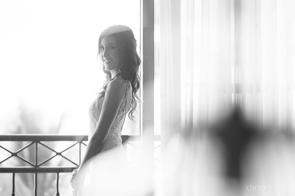The bride is looking fantastic while posing for the camera standing at a balcony of the room- Nikki and David