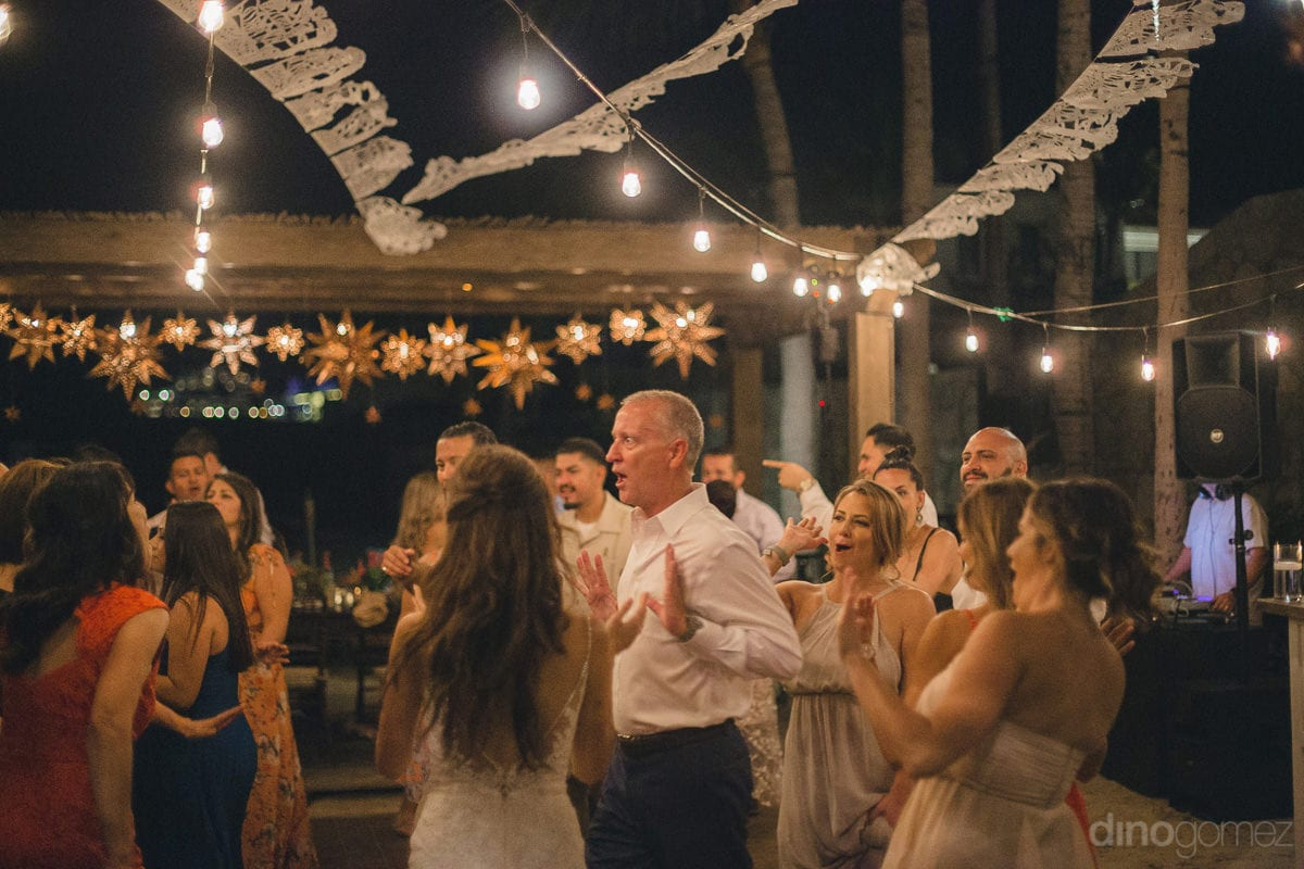 Wedding guests are enjoying the dance party to the fullest at the beachside- Nikki and David