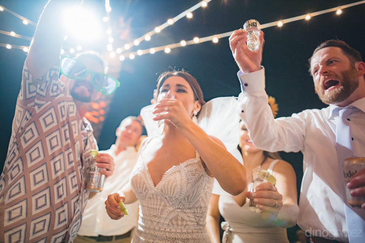 Gorgeous bride is taking drinks along with other wedding guests at the reception party along the beachside- Kathleen & Kevin