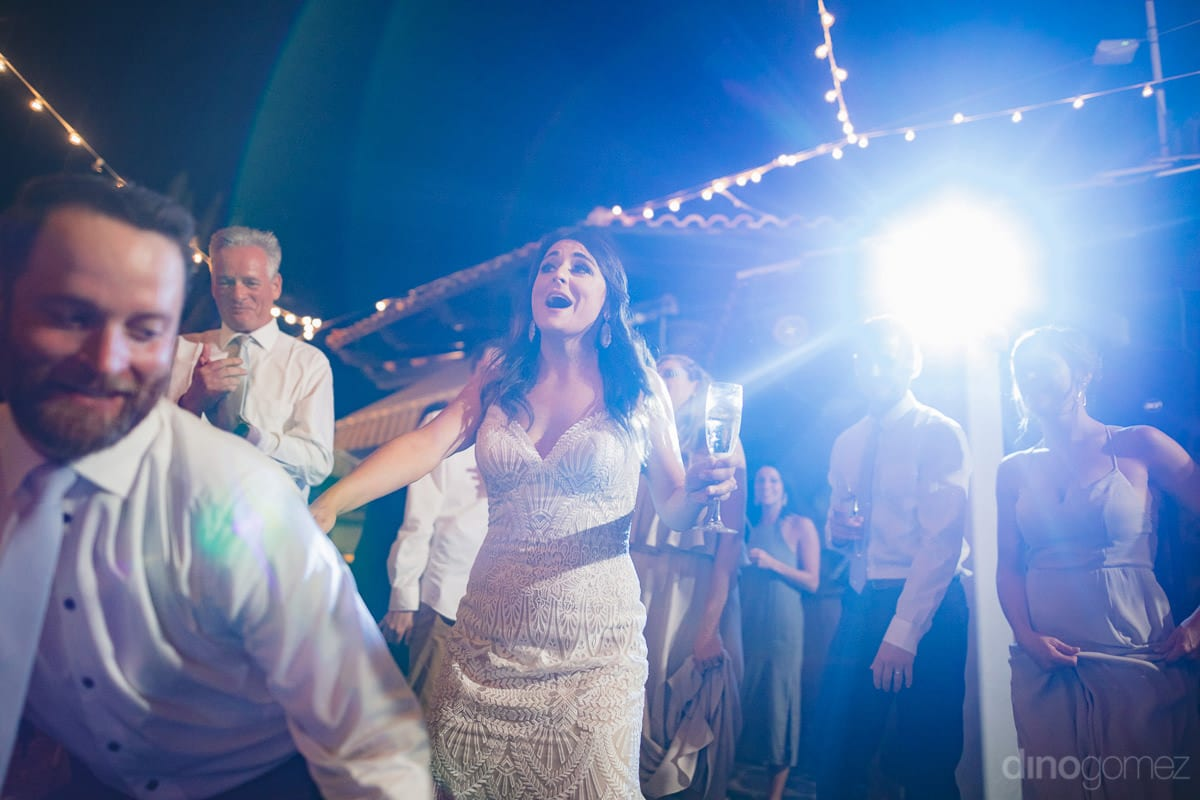 Pretty bride is holding a glass of drink in her hands and is dancing and playing games with the groom at the reception party- Kathleen & Kevin