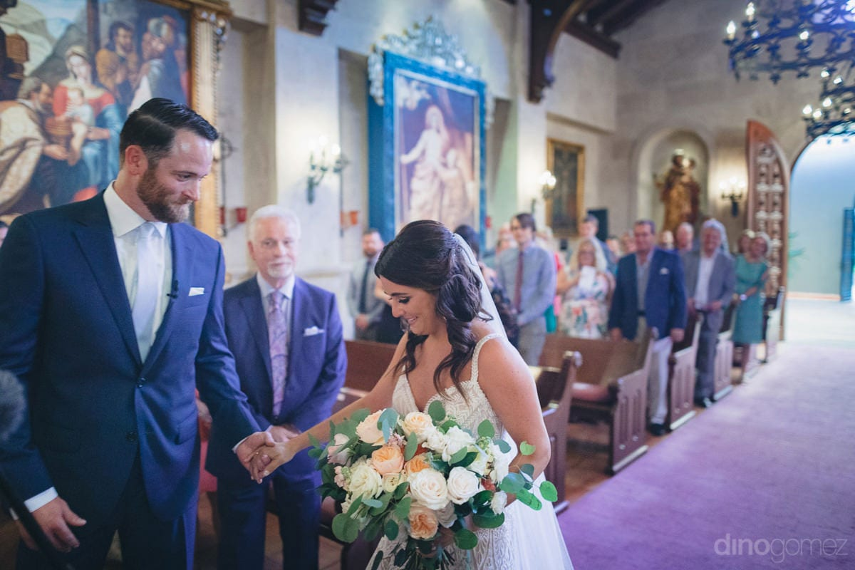 The lovely bride holding her beautiful wedding bouquet can be seen greeted by the handsome groom on the wedding stage- Kathleen & Kevin