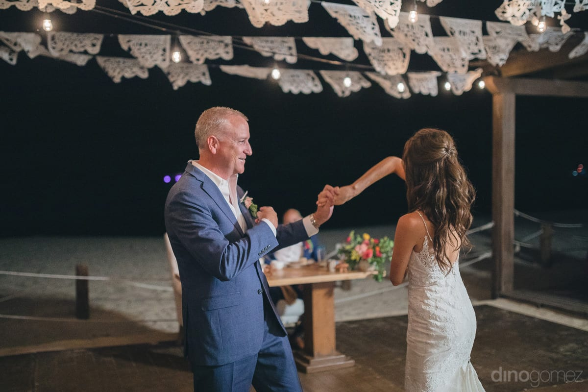 Pretty bride is dancing with a gentleman alone at the dance floor under the dark sky- Nikki and David