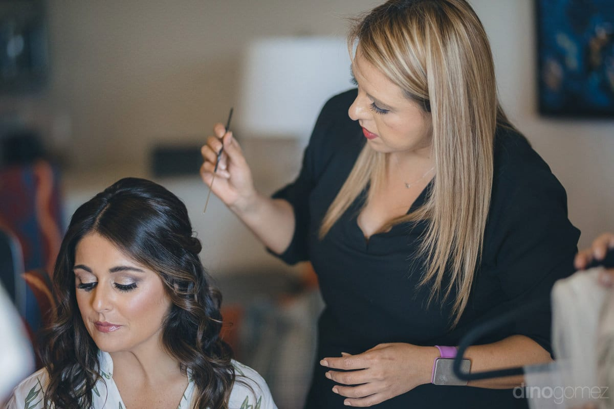 Beautiful Bride Is Sitting On A Chair And Getting Her Hairstyle Done By The Makeup Artist For The Wedding Day- Kathleen & Kevin