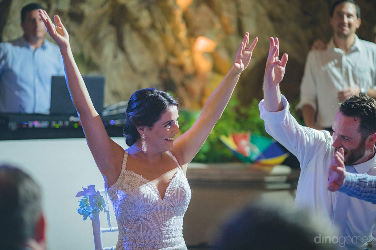 Beautiful bride is dancing with full energy and both the arms in the air along with other guestsat the evening reception party along with other guests- Kathleen & Kevin