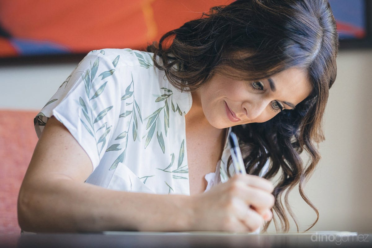A closeup of the beautiful bride while writing something on a piece of paper is taken in the picture- Kathleen & Kevin