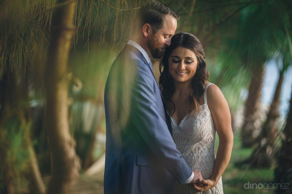 The couple is looking elegant while posing romantically for the camera standing against a big leaf tree- Kathleen & Kevin