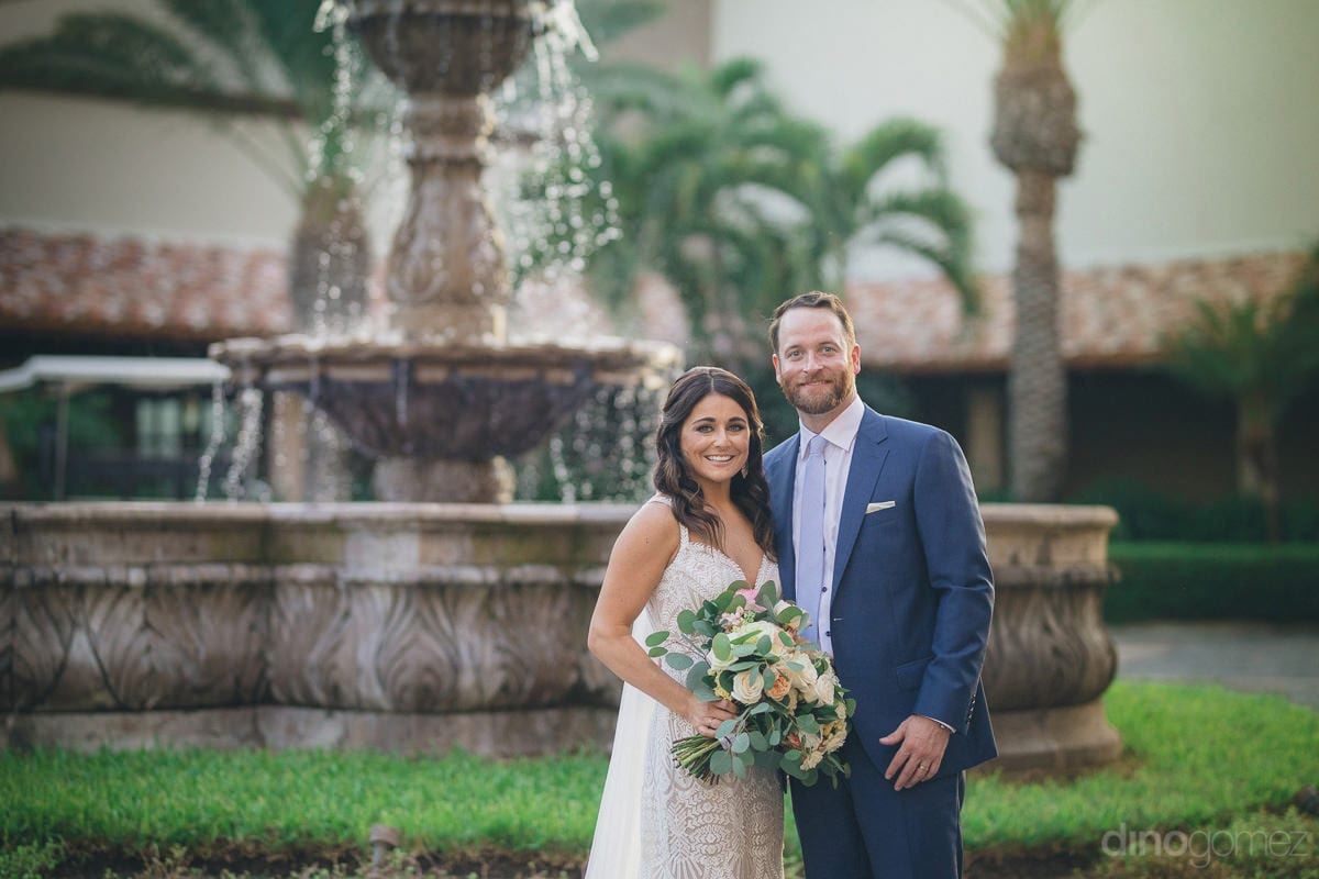 The Couple Is Standing Infront Of A Lovely And Giant Stone Fountain To Pose For The Camera- Kathleen & Kevin