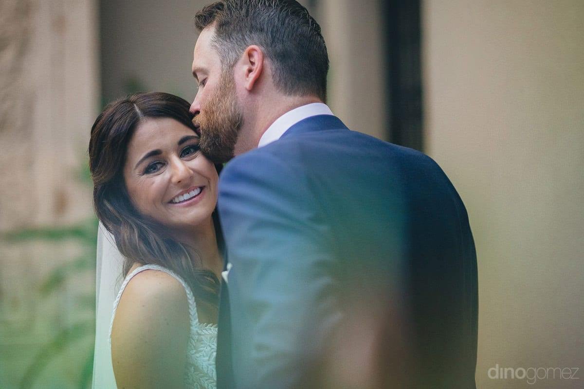 Gorgeous Bride Is Smiling At The Camera While Being Kissed By The Handsome Groom On The Forehead- Kathleen & Kevin