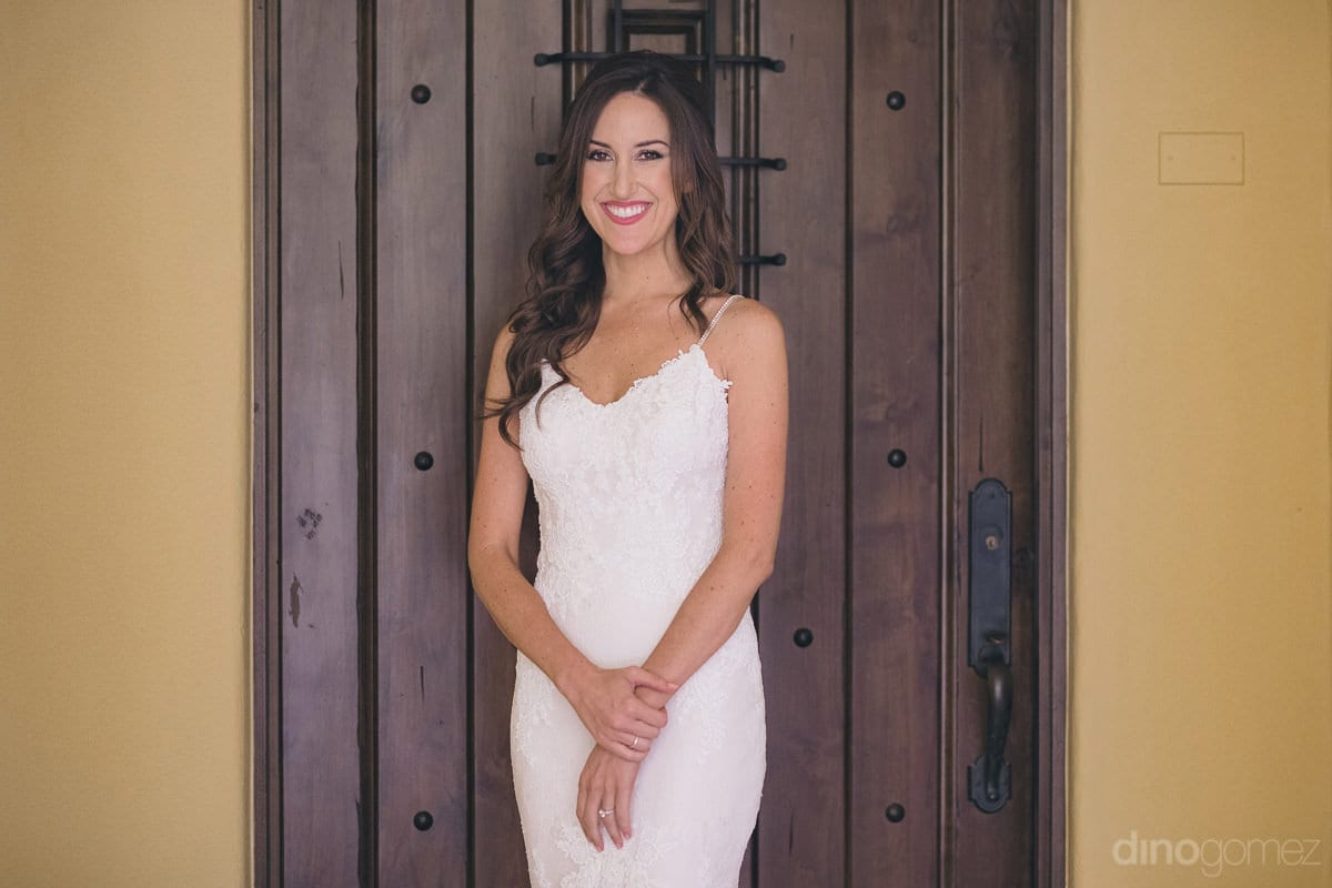 The gorgeous bride is smilingly posing for the camea infront of an antique wooden door- Nikki and David