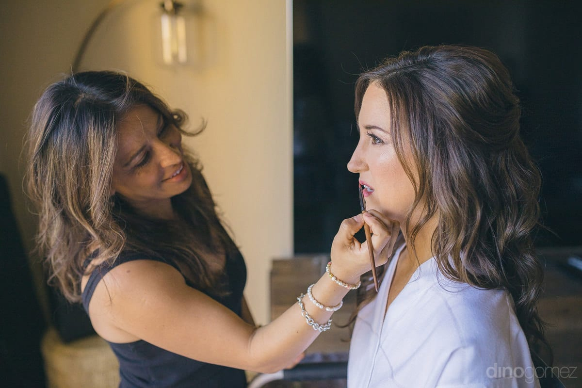 Lovely bride is getting her lip color applied by the makeup artist to get ready for the wedding- Nikki and David