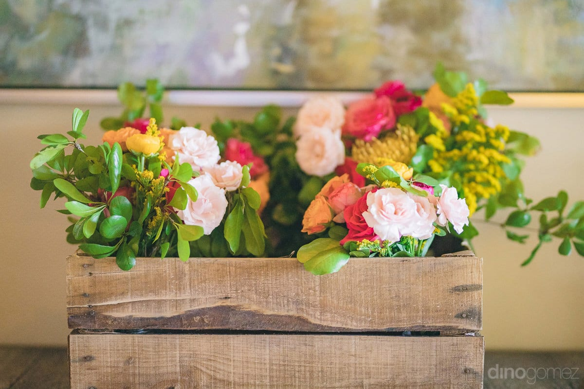 A wooden box containing beautiful roses of different colors is foccused in the picture- Nikki and David