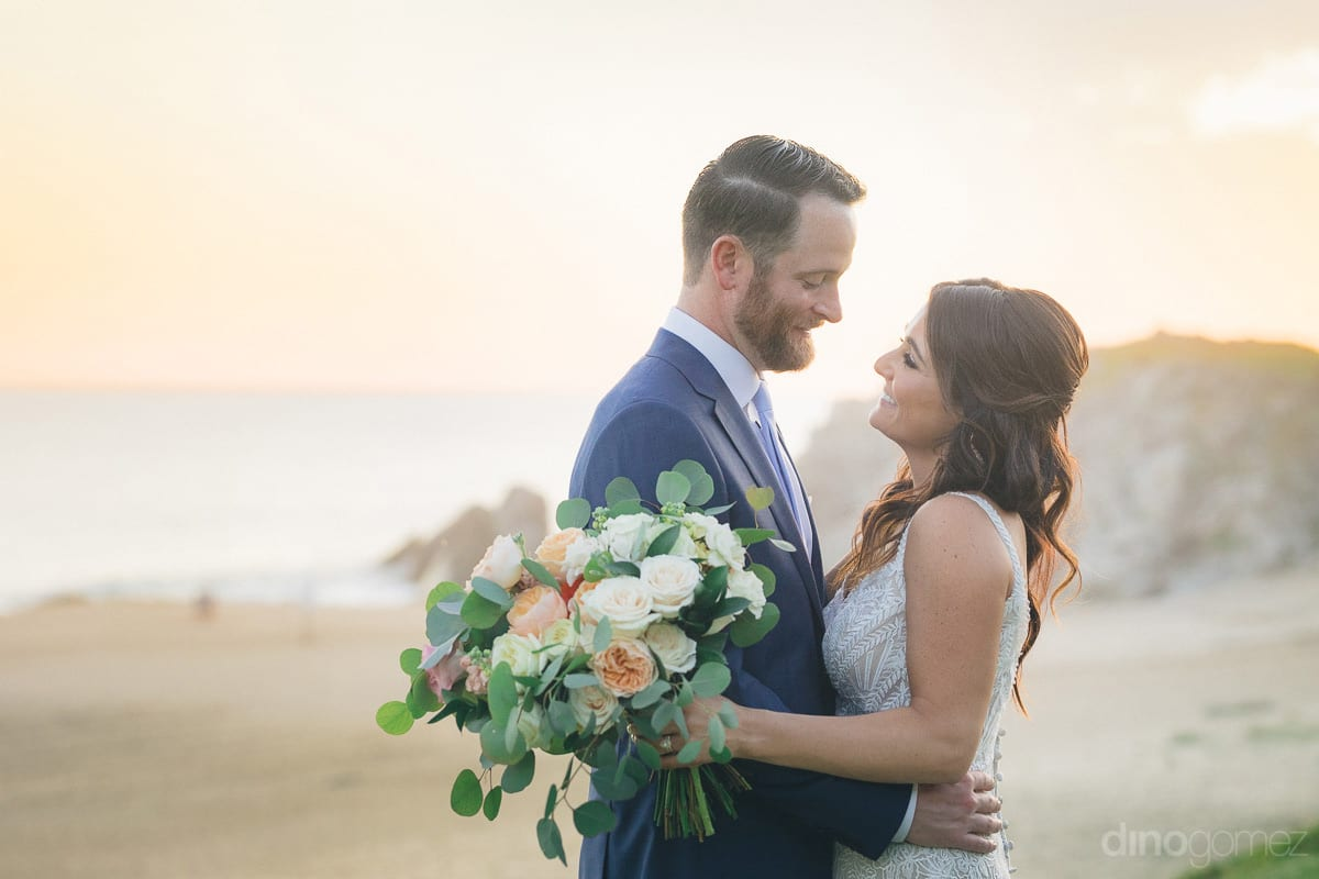 Lovely couple is looking deep into each others eyes while standing at the sea shore during the sunset- Kathleen & Kevin