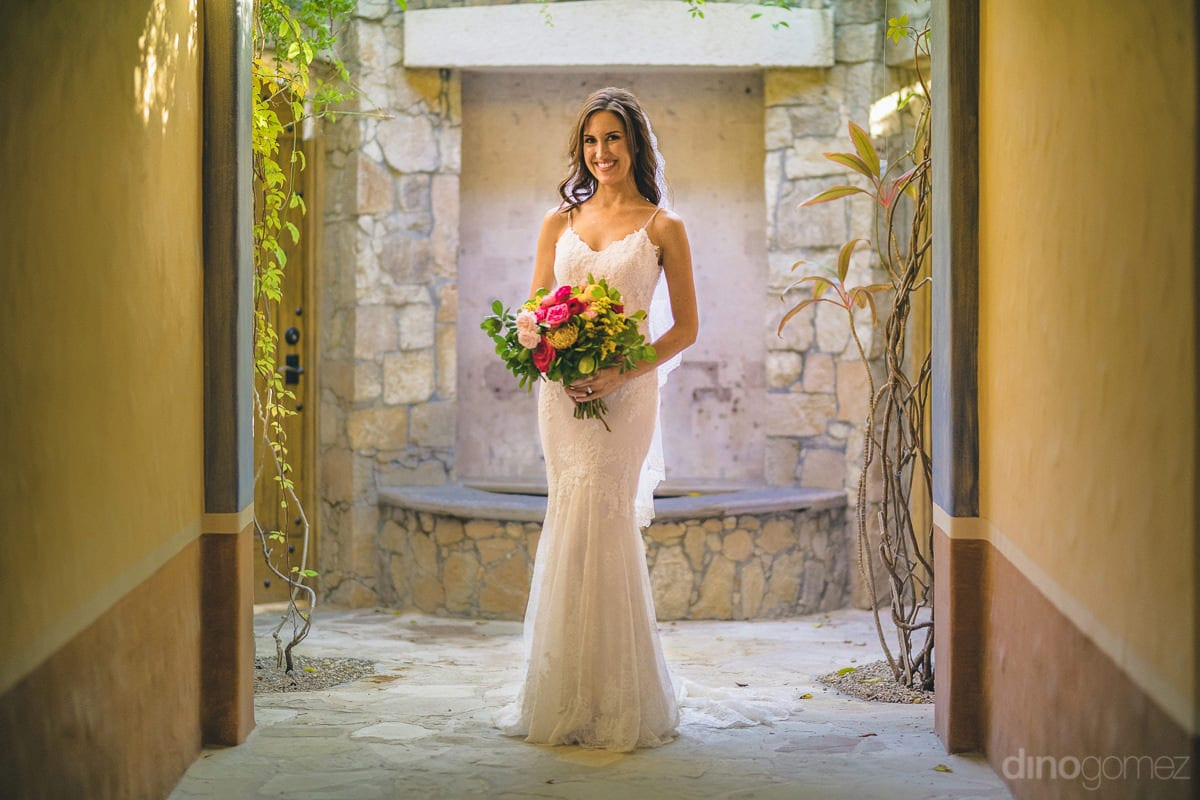 The bride is looking gorgeous in her white wedding gown while standing at a beautiful doorway- Nikki and David