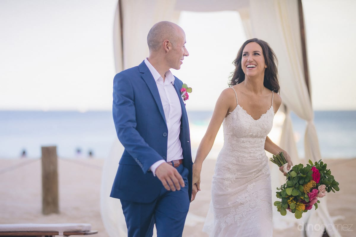 Gorgeous couple is laughing loudly while walking at the beachside after the completion of wedding ceremonies- Nikki and David