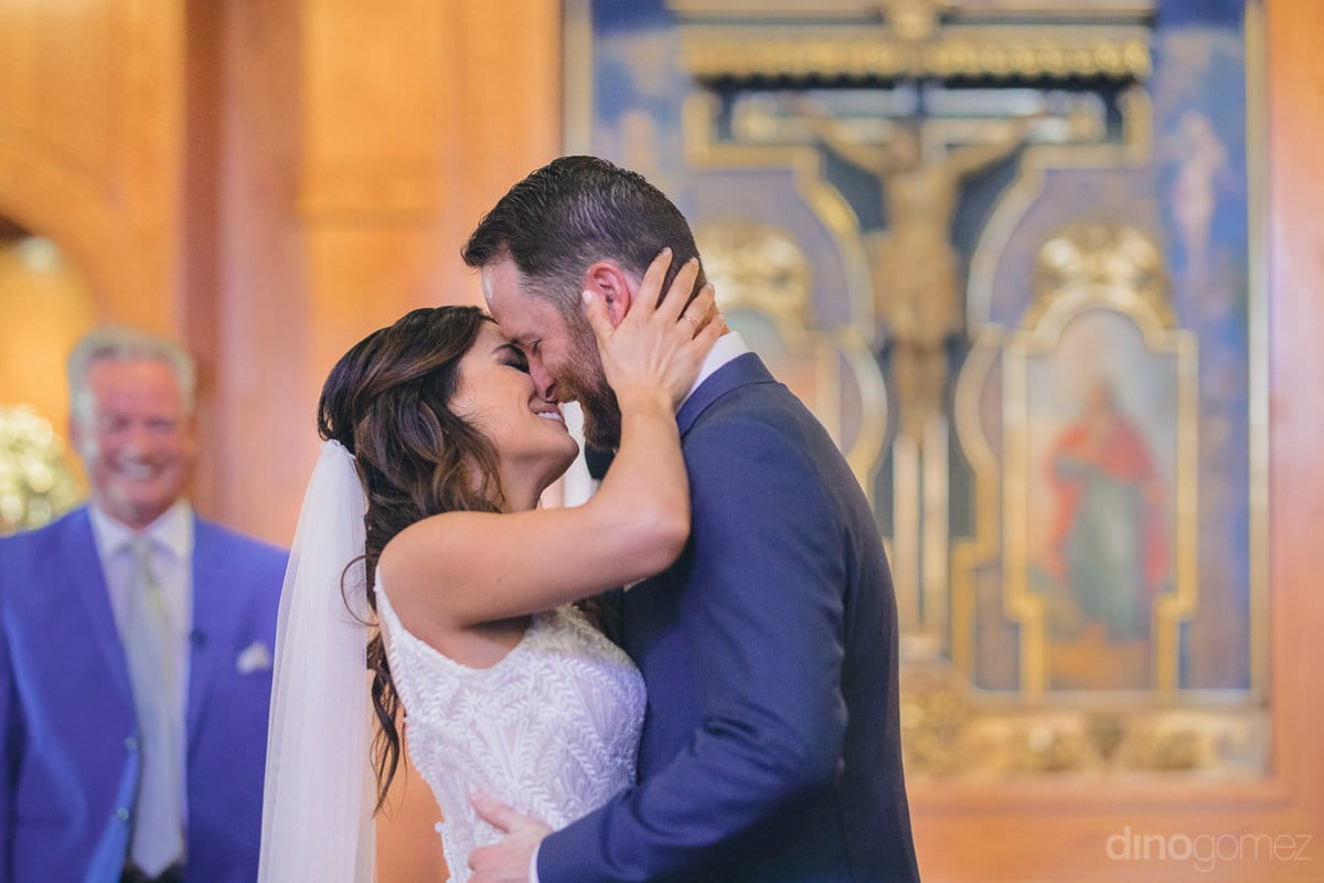 The Lovely Couple Is About To Kiss Each Other Standing Inside The Church Infront Of The Guests- Kathleen & Kevin
