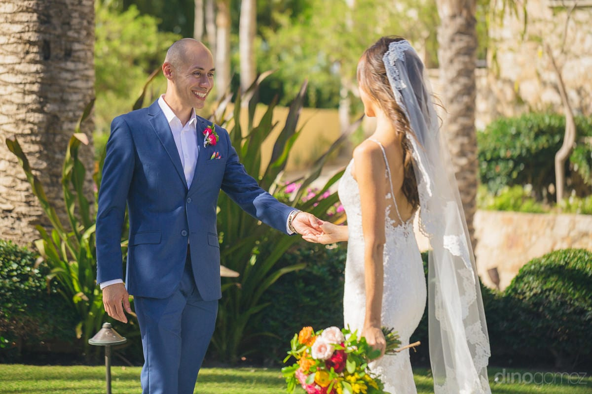 Handosme groom is holding one hand of the lovely bride with a big smile on his face- Nikki and David