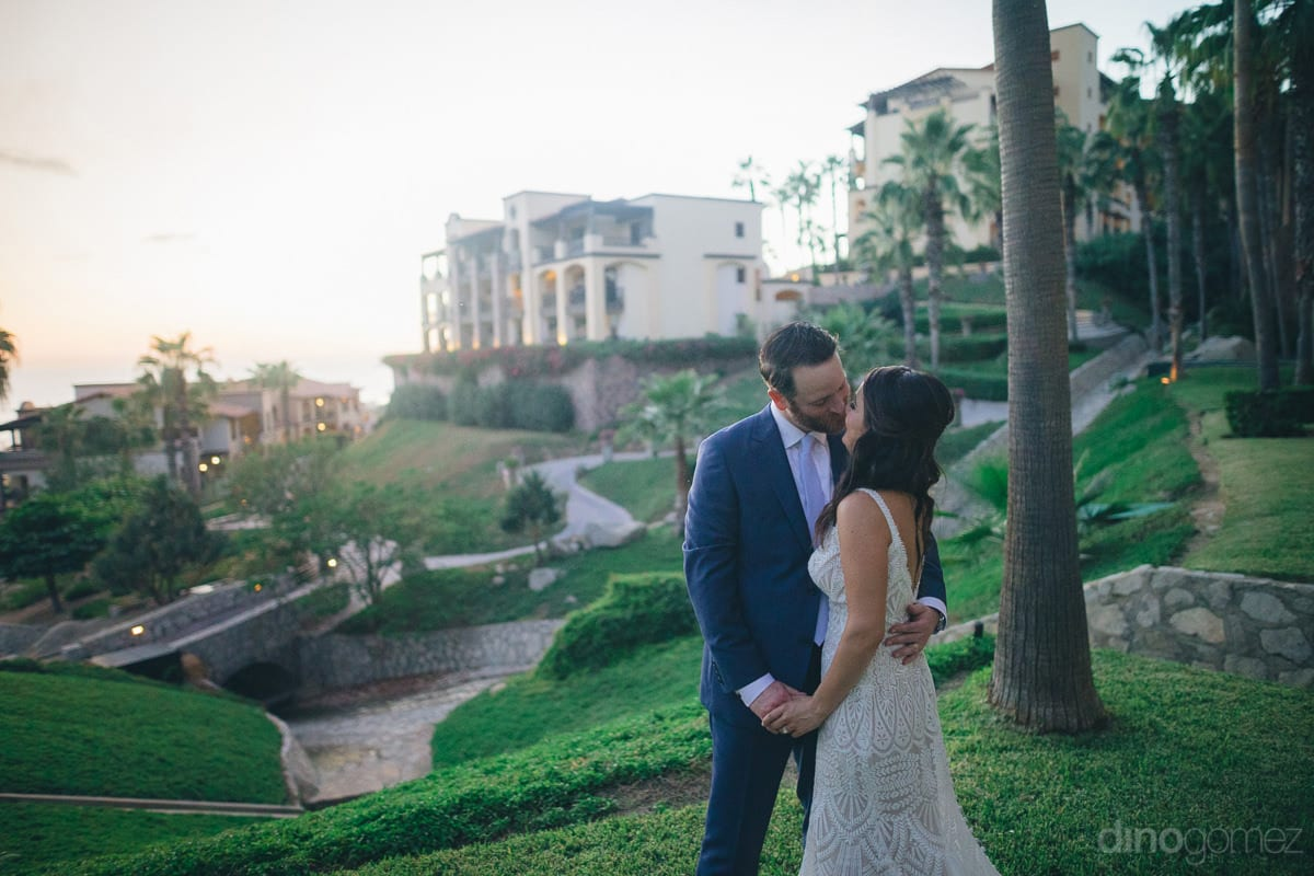 The Beautiful Couple Is Kissing Each Other Standing At The Luxurious Lawn Of The Beachside Palace- Kathleen & Kevin