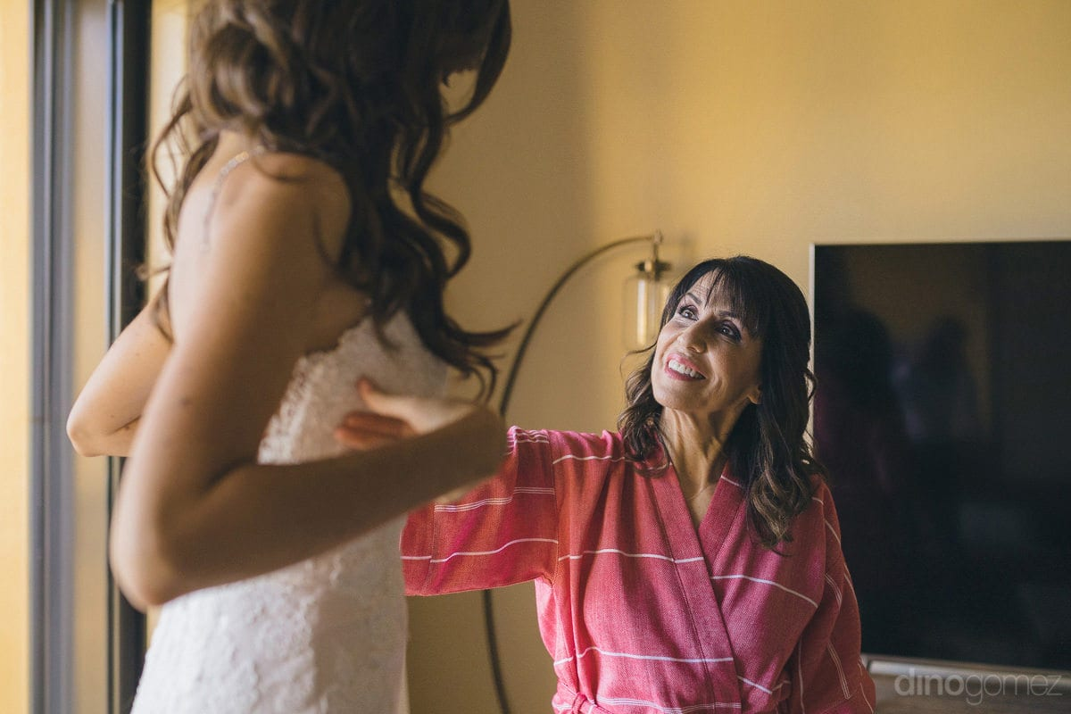 Gorgeous bride is sitting inside the room and is talking to a lady while setting her wedding gown- Nikki and David