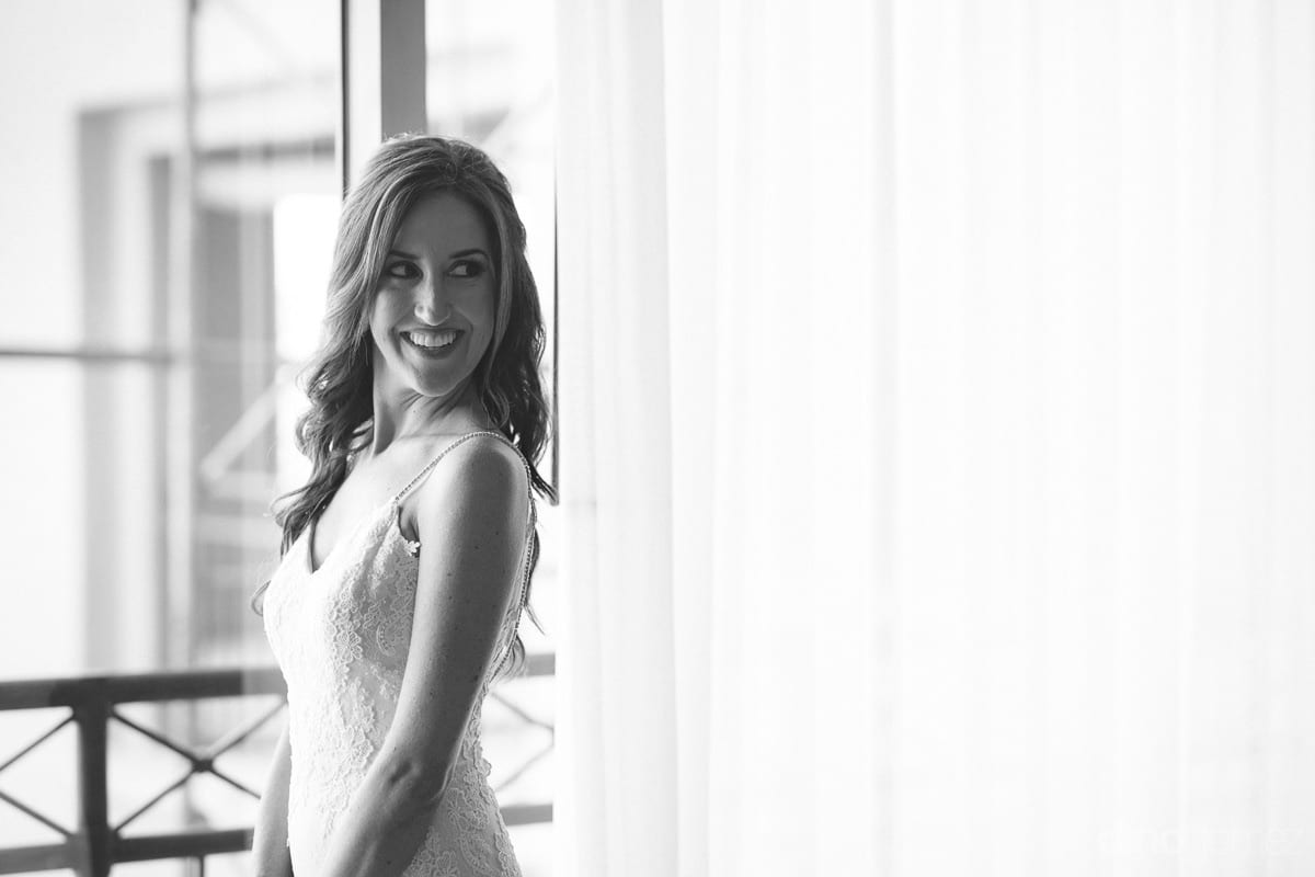 The gorgeous bride is giving a fantastic pose standing inside the palace room for the camera- Nikki and DavidThe lovely bride is giving a fantastic pose by smiling and standing at the windoside of the room. The picture is in black and white colors to giv